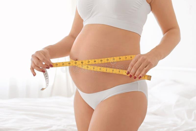 Zwangere vrouw die haar buik meet stock afbeelding