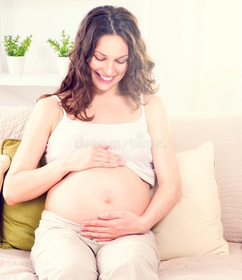 Zwangere vrouw die haar buik streelt stock afbeelding