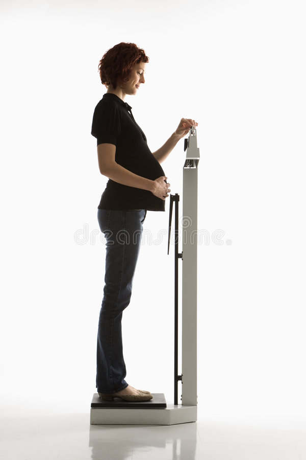 Zwangere vrouw die haar gewicht controleert. stock afbeelding