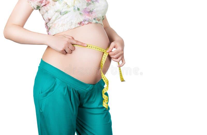 Zwangere vrouw die haar taille en maag meten stock afbeelding