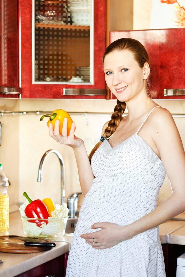 Zwangere vrouw die in keuken een salade maakt royalty-vrije stock fotografie