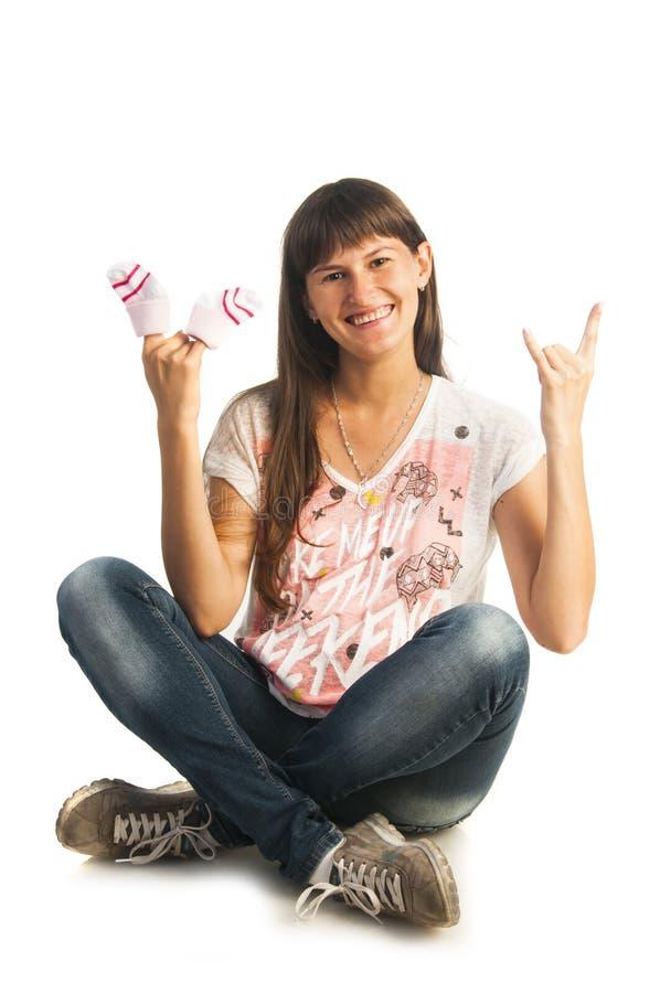 Zwangere vrouw die kleine sokken houden stock fotografie