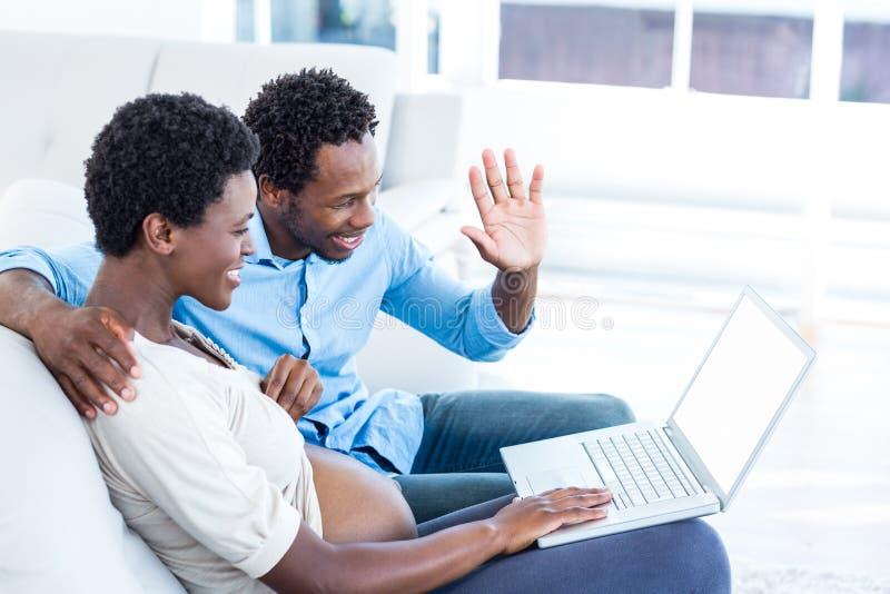 Zwangere vrouw die laptop met behulp van terwijl het zitten door echtgenoot stock afbeelding