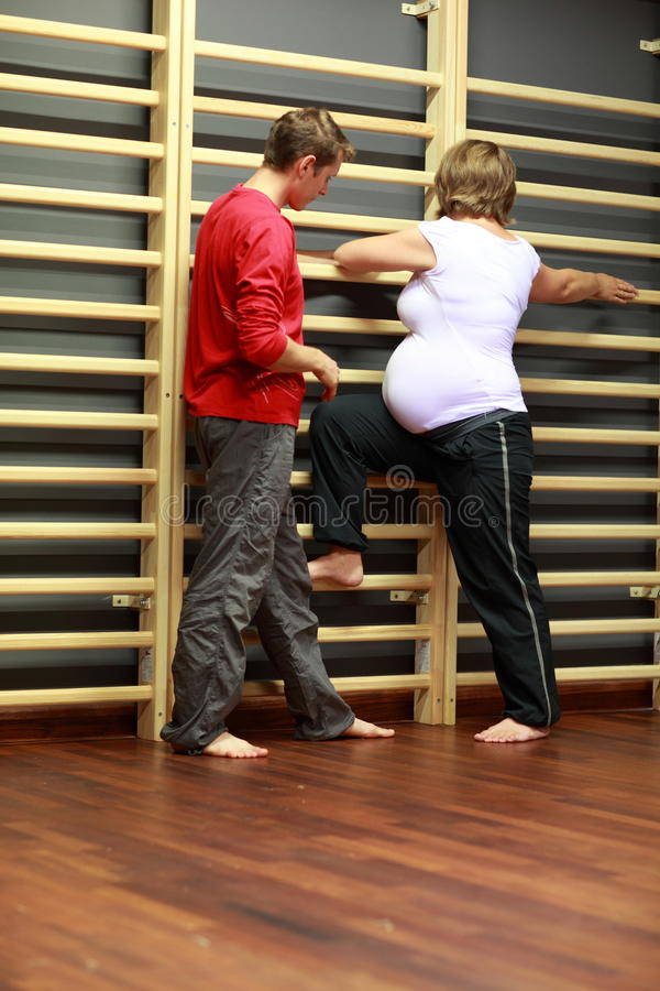 Zwangere vrouw die met instructeur uitoefent stock foto's