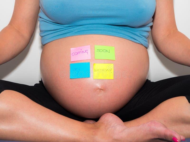 Zwangere vrouw die met spoedig mijn verjaardagsbericht op haar buik komen royalty-vrije stock foto