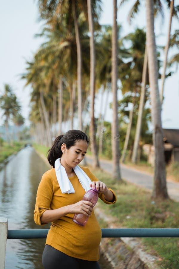 Zwangere vrouw die na training een fles water drinken royalty-vrije stock foto
