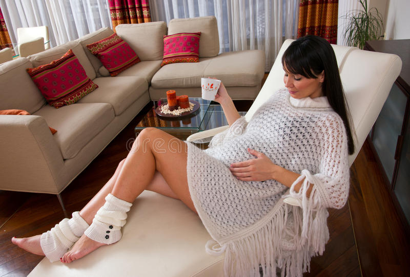 Zwangere vrouw die op bank rust royalty-vrije stock foto