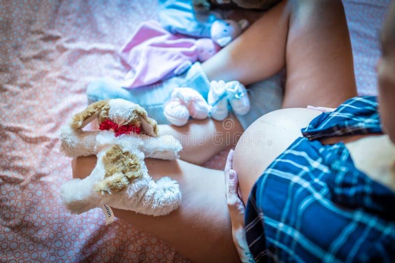 Zwangere Vrouw die op Bed haar Buik strelen Speelgoed en Schoenen rond stock foto