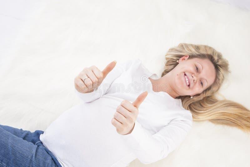 Zwangere Vrouw die op Bonttapijt leggen in Witte Overhemd en Jeans stock afbeelding