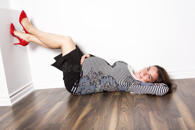 Zwangere vrouw die op de vloer leggen stock fotografie
