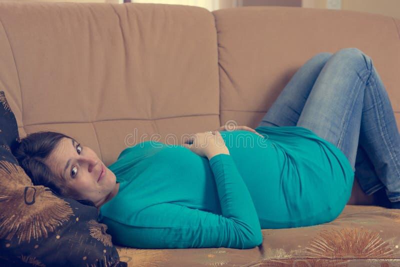 Zwangere vrouw die op een laag rusten royalty-vrije stock foto's