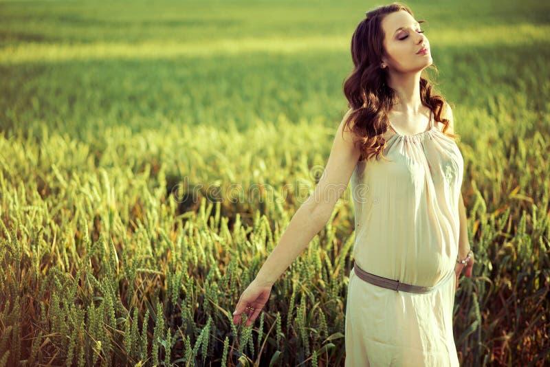 Zwangere vrouw die op het graangebied lopen stock fotografie