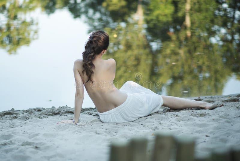 Zwangere vrouw die op het strand liggen stock afbeeldingen