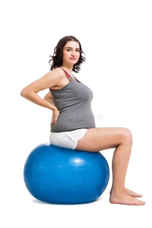 Zwangere vrouw die pilates oefeningen doen stock foto