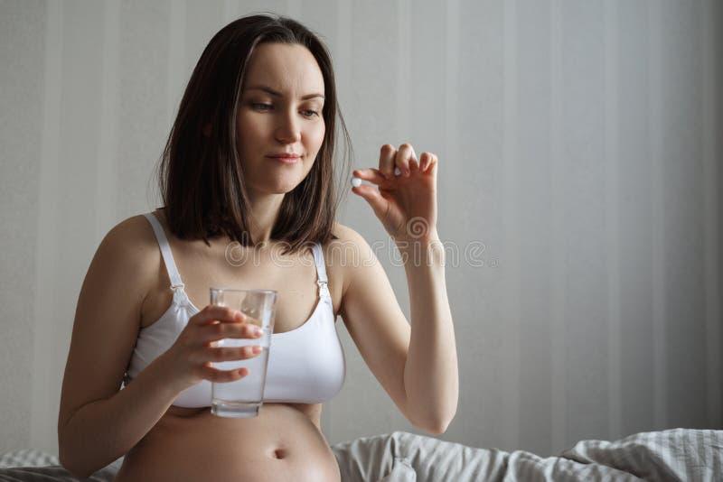 Zwangere vrouw die pillen op grijze achtergrond nemen royalty-vrije stock foto