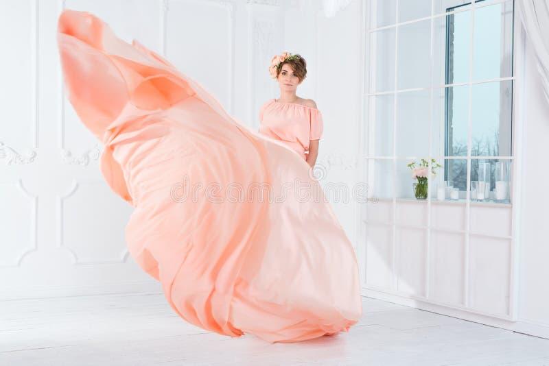 Zwangere vrouw die in roze avondjurk dansen die op wind vliegen Golvende stof, manierschot stock afbeelding