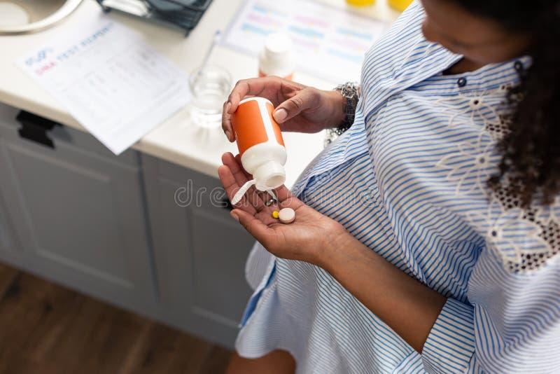 Zwangere vrouw die sommige vitaminen gaan nemen stock afbeelding
