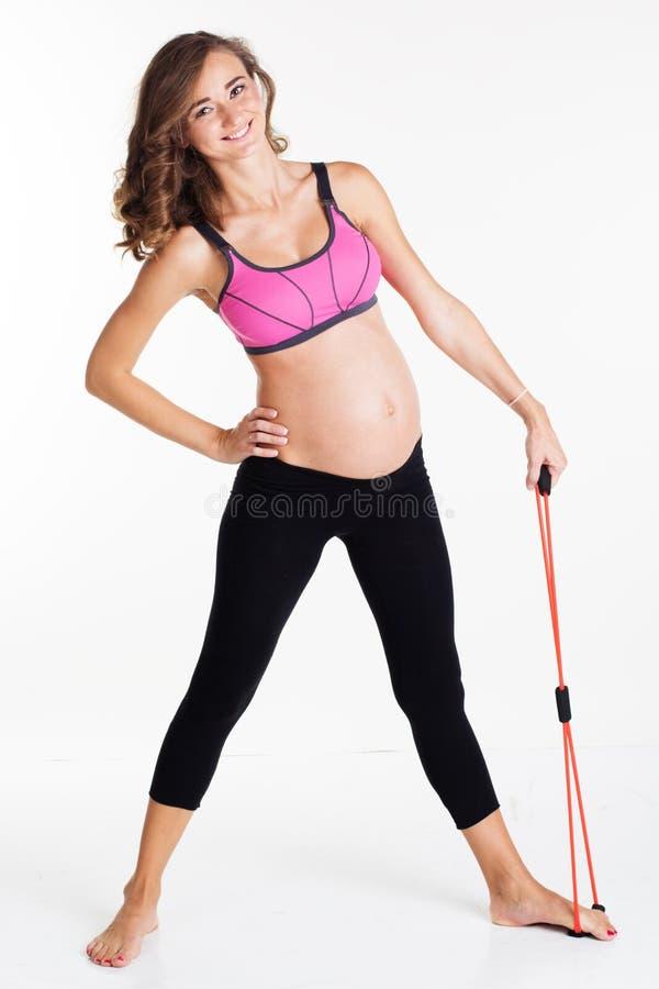 Zwangere vrouw die sport met weerstandsband doen stock afbeeldingen