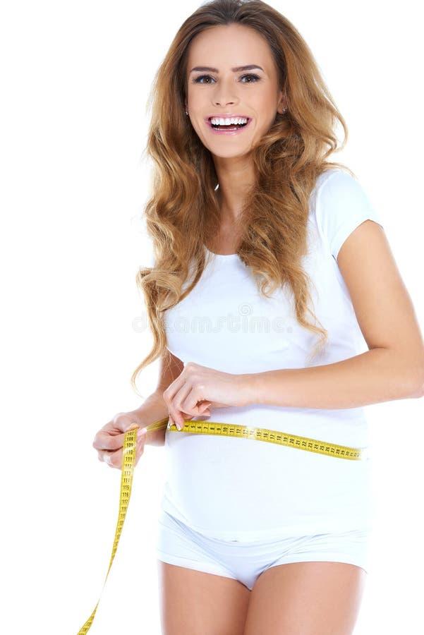Zwangere Vrouw die Taille met Meetlint meten stock afbeeldingen