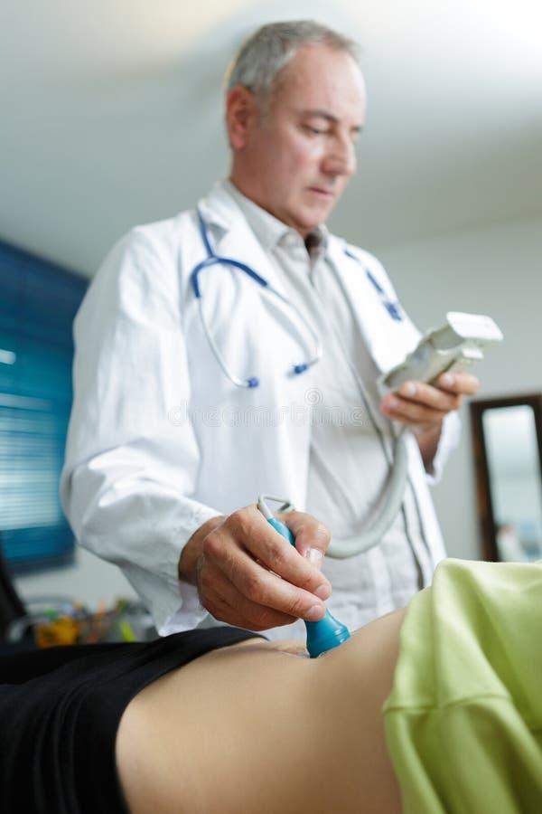 Zwangere vrouw die ultrasone klank van arts in kliniek krijgen stock afbeeldingen