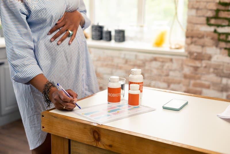 Zwangere vrouw die van alle vitaminen nota nemen zij die nemen royalty-vrije stock afbeelding