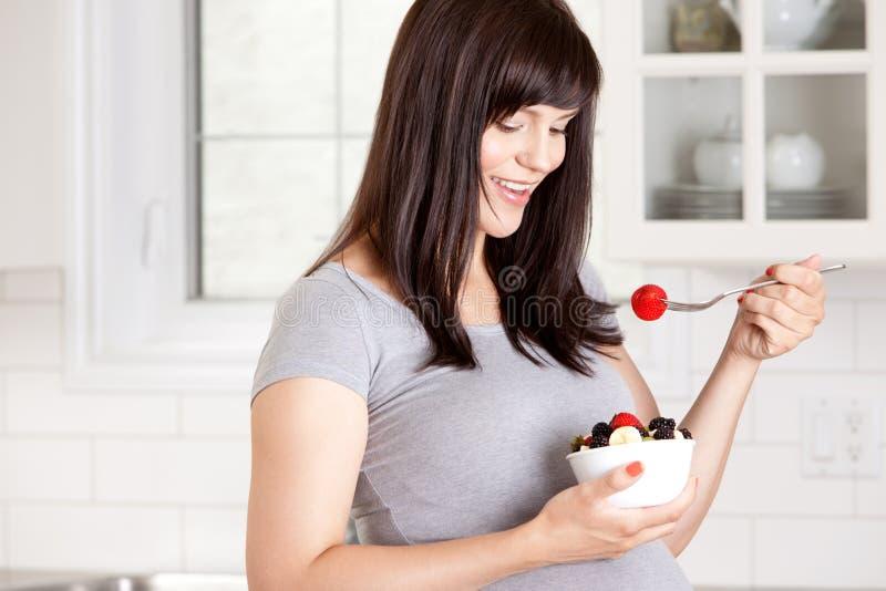 Zwangere Vrouw die Vers Fruit eten stock afbeelding