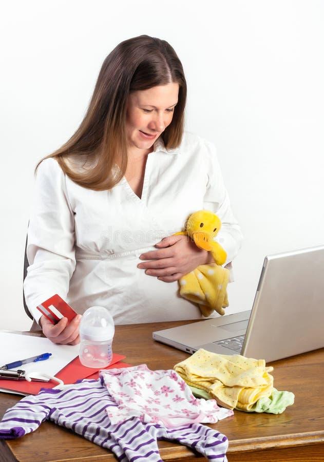 Zwangere Vrouw die voor Babylevering online winkelen stock fotografie