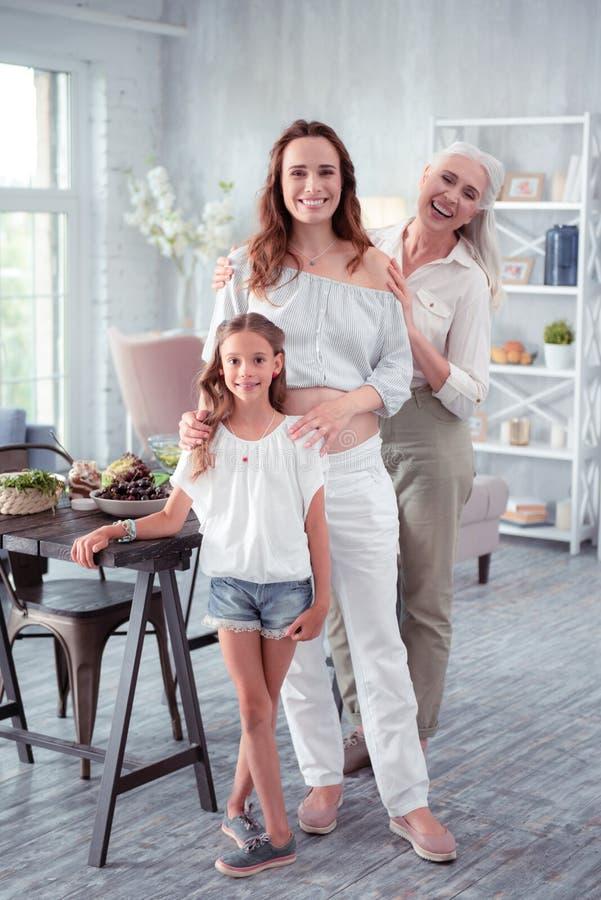 Zwangere vrouw die vrolijke status voelen dichtbij dochter en moeder royalty-vrije stock afbeelding