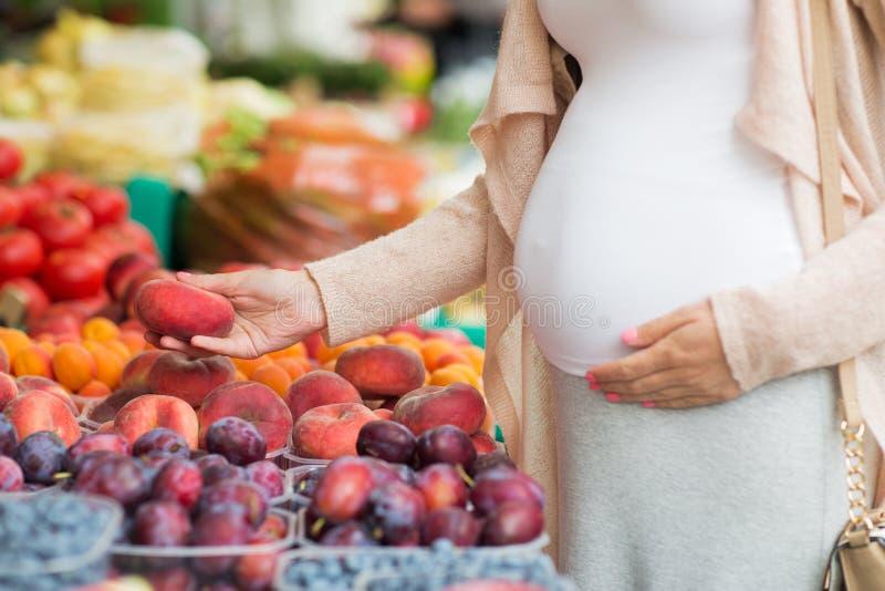 Zwangere vrouw die vruchten kiezen bij straatmarkt royalty-vrije stock afbeeldingen