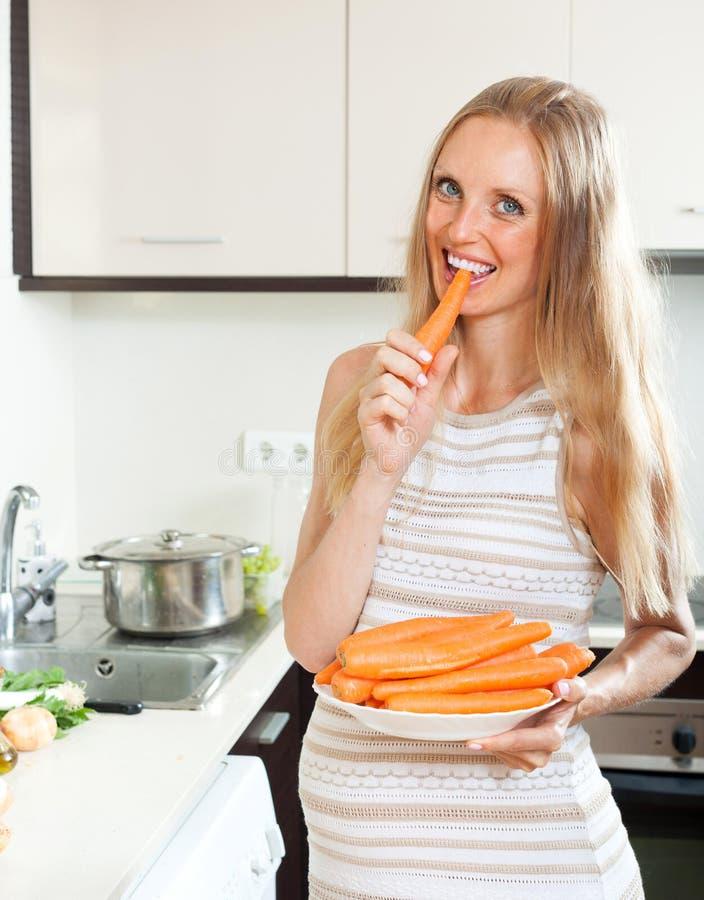 Zwangere vrouw die wortel eten stock afbeeldingen
