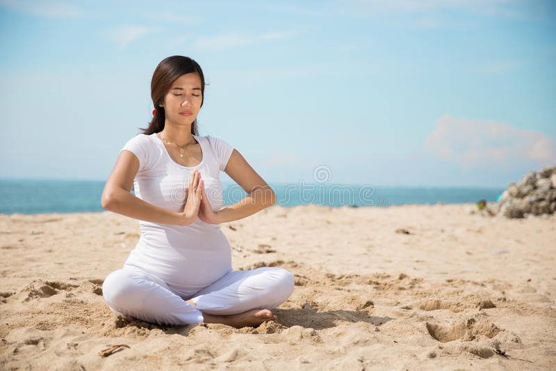 Zwangere vrouw die yoga in het strand doen royalty-vrije stock foto
