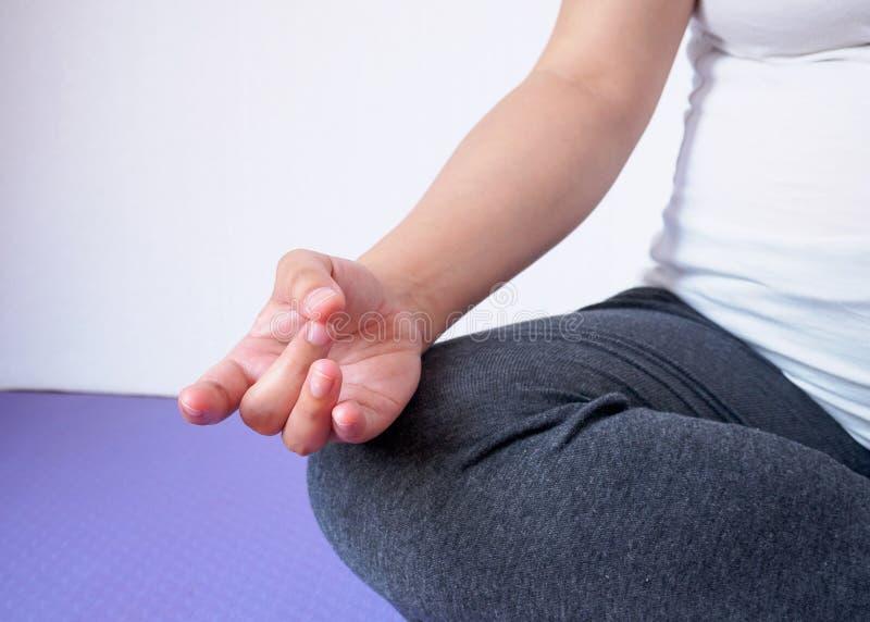 Zwangere vrouw die yoga thuis doet royalty-vrije stock afbeelding