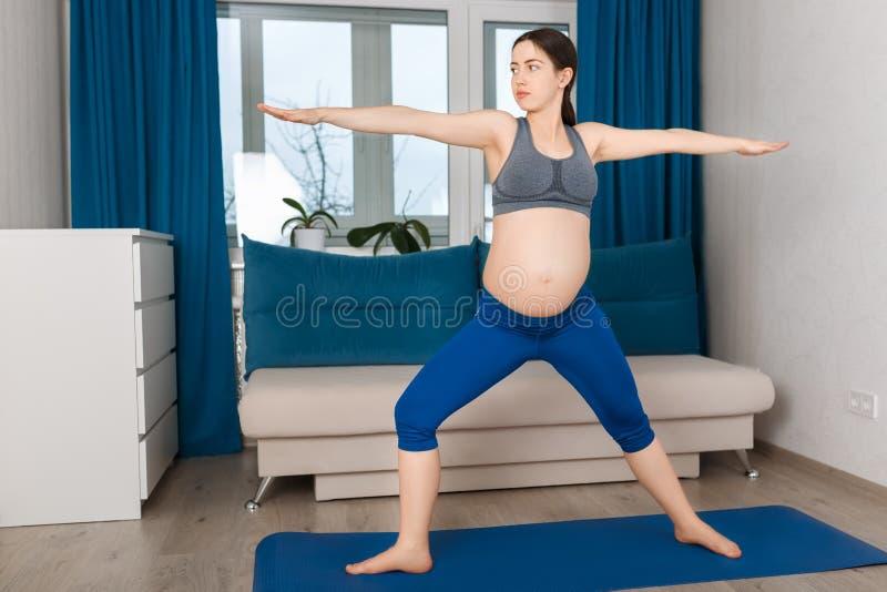 Zwangere vrouw die yogaoefening doet royalty-vrije stock foto