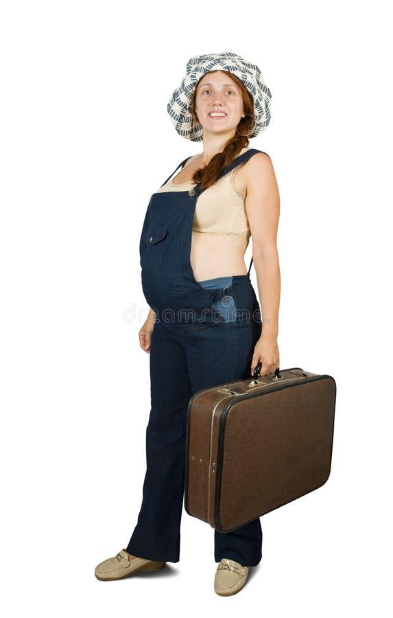 Zwangere vrouw die zich met koffer bevindt royalty-vrije stock foto's