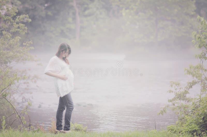 Zwangere vrouw door mistige rivier stock afbeelding
