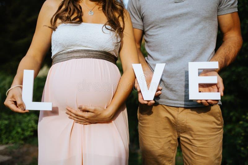 zwangere vrouw en haar echtgenoot die de brieven voor liefde in hun handen houden met royalty-vrije stock afbeelding