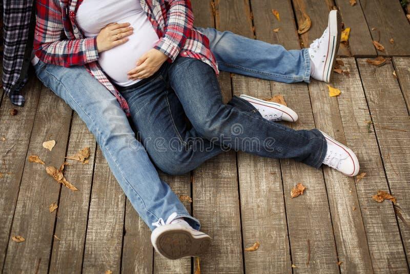 Zwangere vrouw en haar echtgenoot die op de houten vloer liggen stock foto's