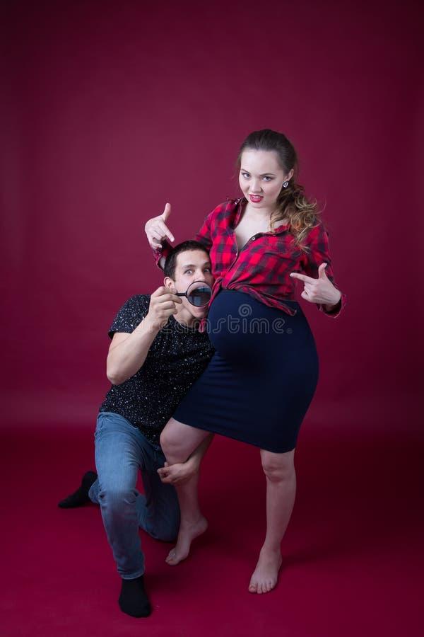 Zwangere vrouw en haar echtgenoot op een rode achtergrond royalty-vrije stock foto