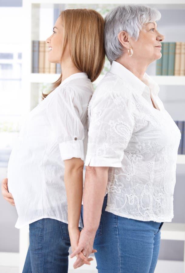 Zwangere vrouw en moeder die zich rijtjes bevinden stock afbeeldingen