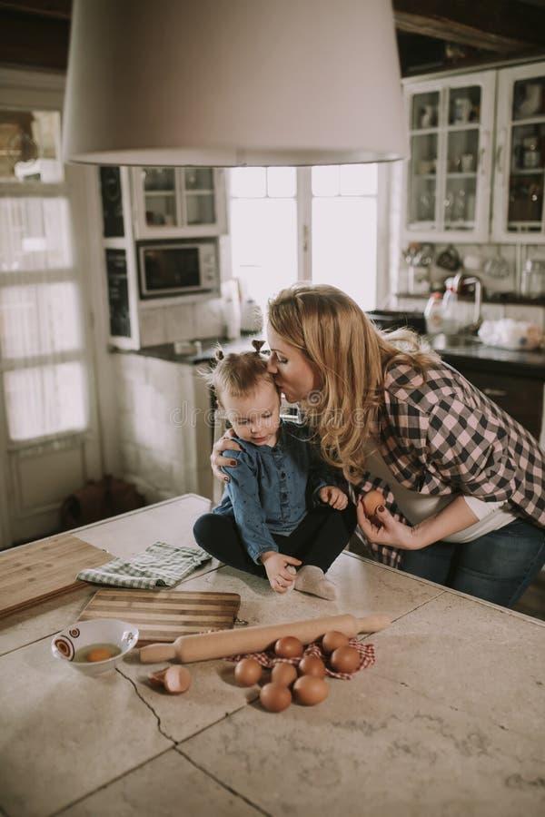 Zwangere vrouw en weinig dochter in de rustieke keuken royalty-vrije stock fotografie