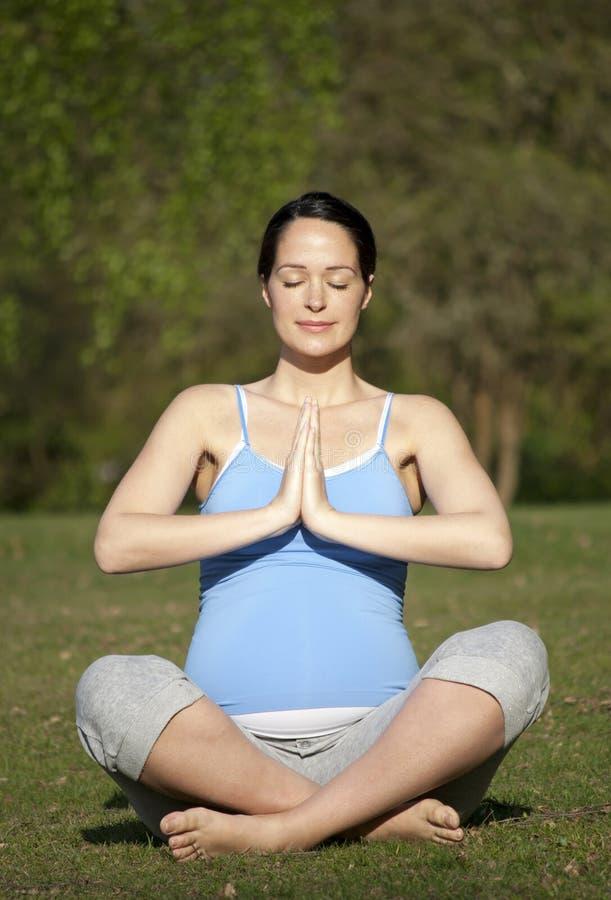 Zwangere vrouw het praktizeren yoga royalty-vrije stock foto's