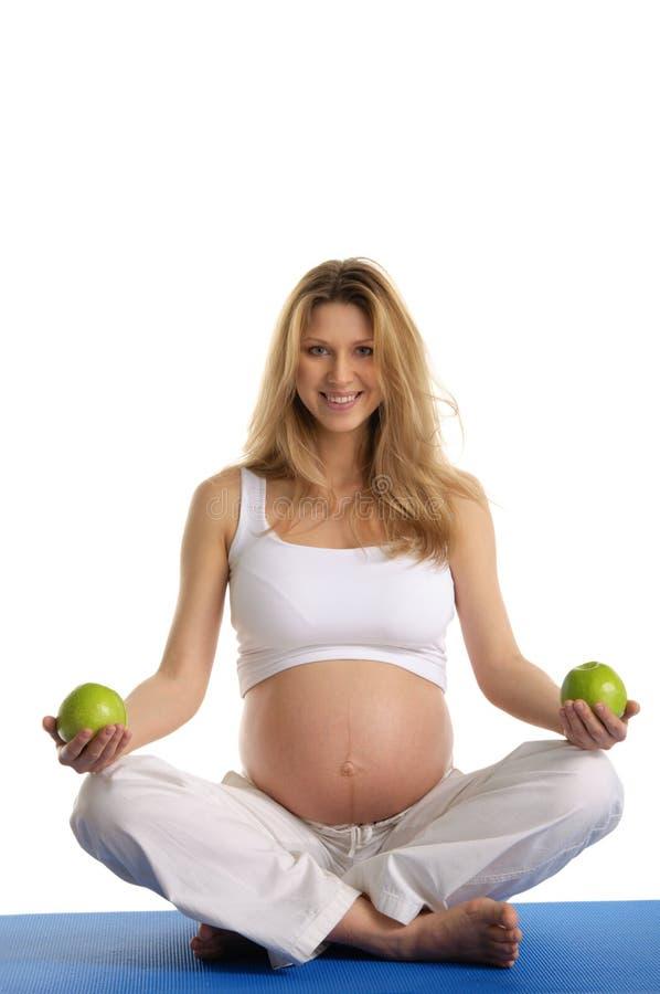 Zwangere vrouw het praktizeren yoga en levensonderhoudappelen royalty-vrije stock afbeelding