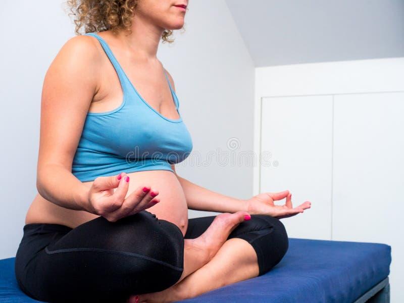 Zwangere vrouw het praktizeren Yoga en meditatie in lotusbloemhouding ( royalty-vrije stock afbeeldingen