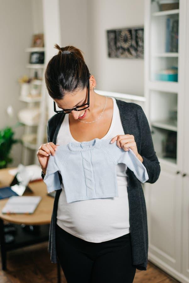 Zwangere vrouw het winkelen babykleren van huis royalty-vrije stock afbeeldingen