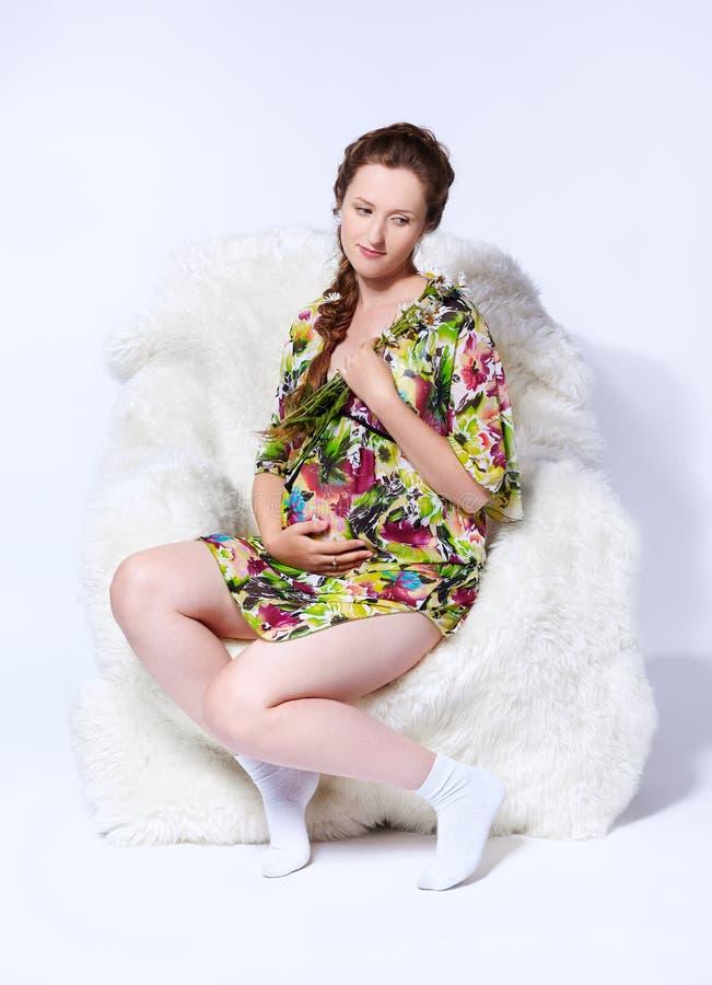 Zwangere vrouw in leunstoel royalty-vrije stock foto
