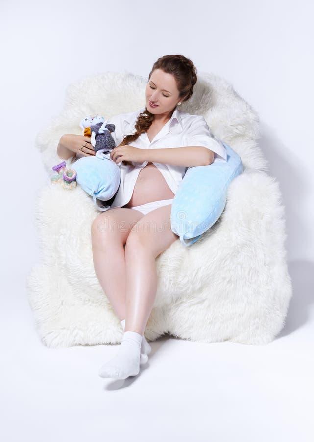 Zwangere vrouw in leunstoel stock fotografie