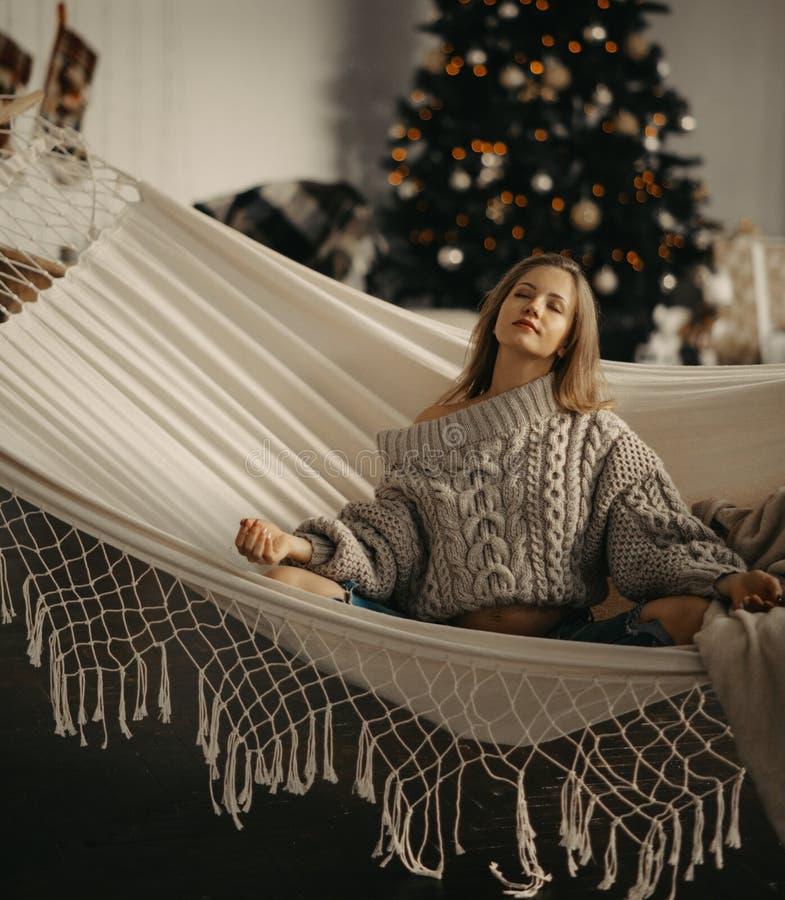 Zwangere vrouw mediteert in hammock tegen de achtergrond van de kerstboom royalty-vrije stock foto