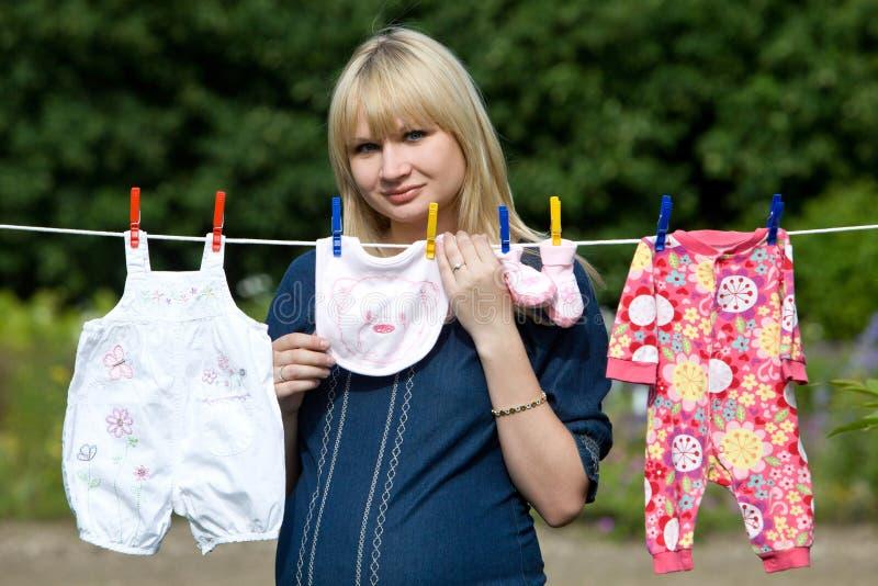 Zwangere vrouw met babykleren baby kleren op een drooglijn royalty-vrije stock foto's