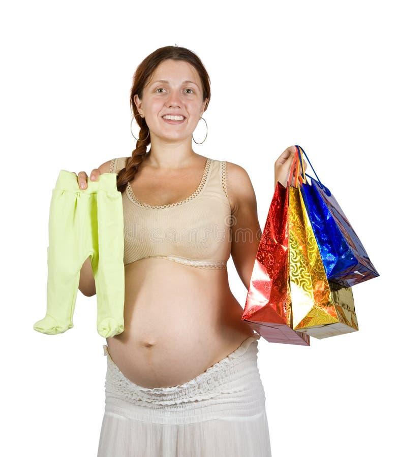 Zwangere vrouw met de kleren van de baby royalty-vrije stock fotografie