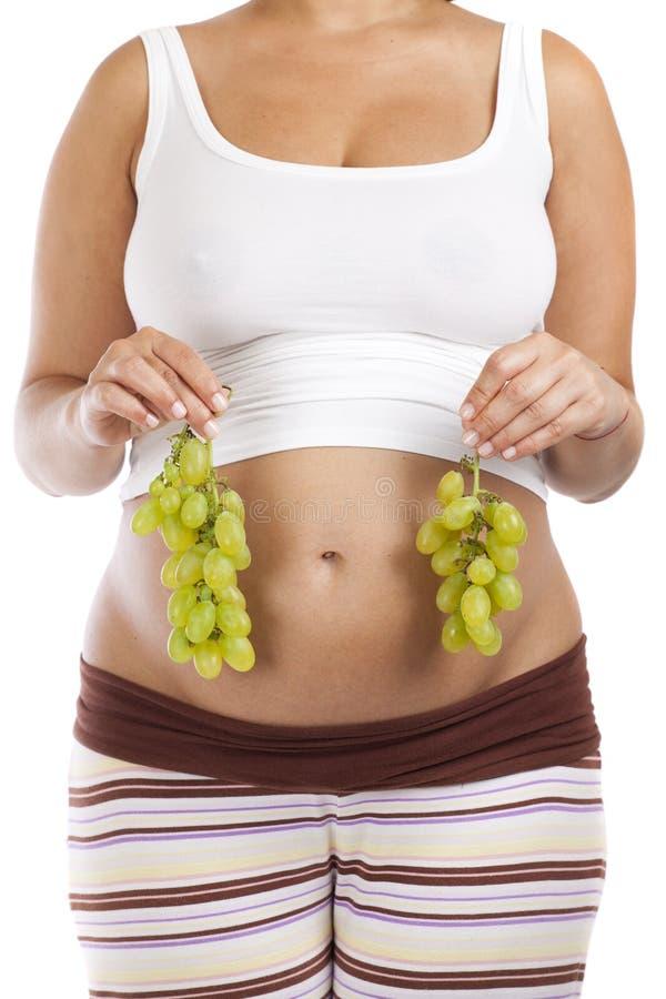 Zwangere vrouw met druif royalty-vrije stock afbeeldingen